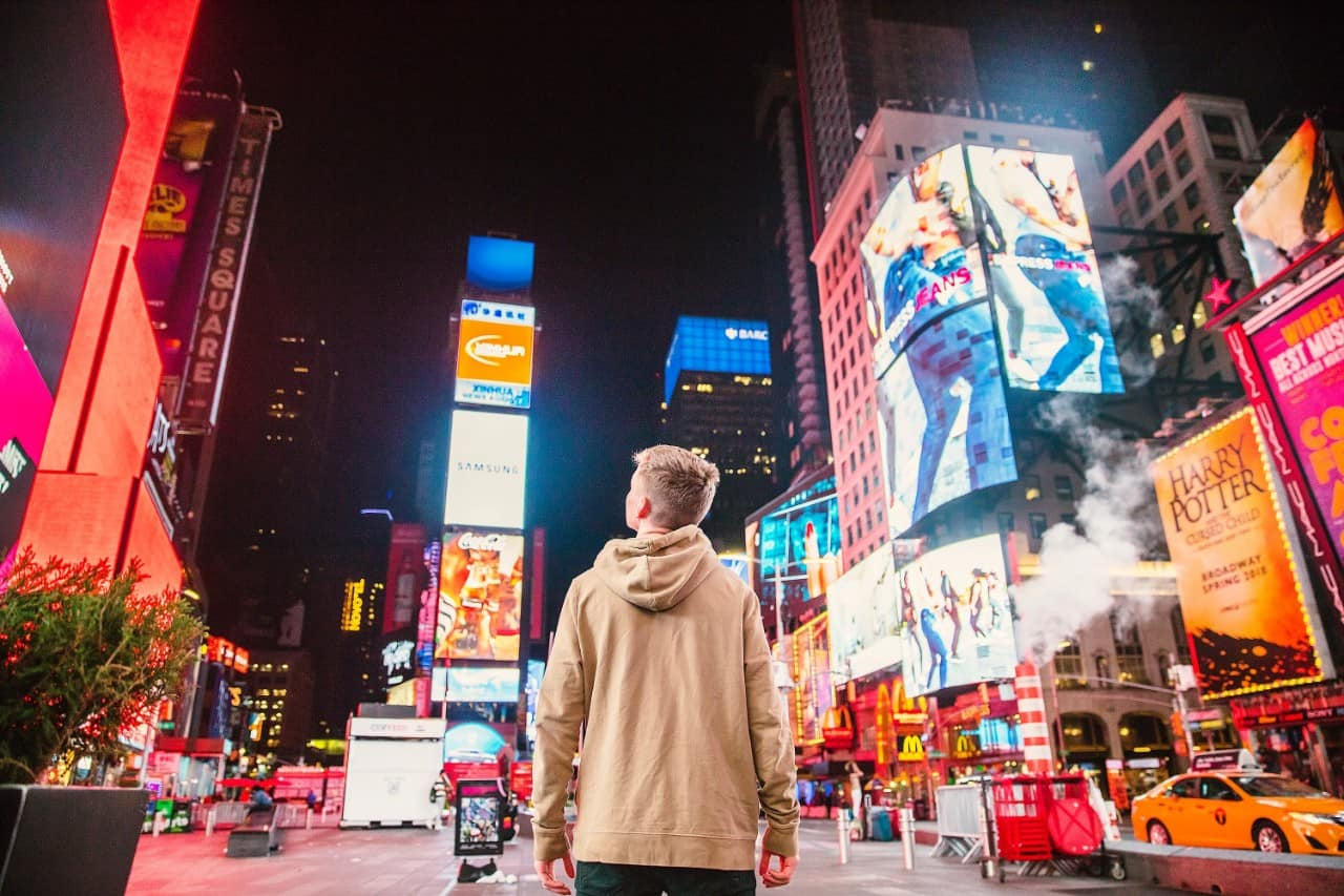 man standing in the middle of times square at night